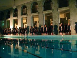 Grex Musicus -kuoro uima-altaan reunalla hämärässä valaistuksessa päällään mustat esiintymisasut.