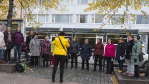Vaput -kuoro laulamassa puiden välissä kivetyllä kadulla kerrostalon edessä.
