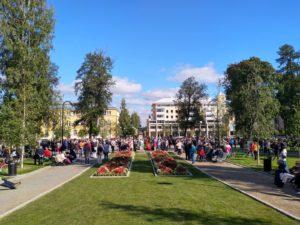 Ihmisiä kuuntelemassa kuoroja puistossa