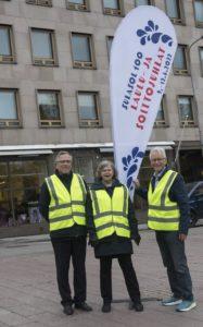 Kolme ihmistä huomioliivit päällä pisaranmuotoisen Laulu- ja Soittojuhlien mainoslipun edessä.